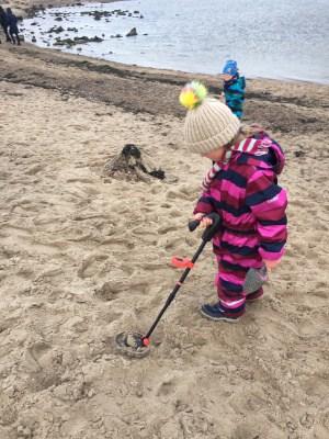 Kind mit Metalldetektor am Strand